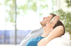 Side view of a happy couple breathing and resting lying in a couch at home with a window in the background